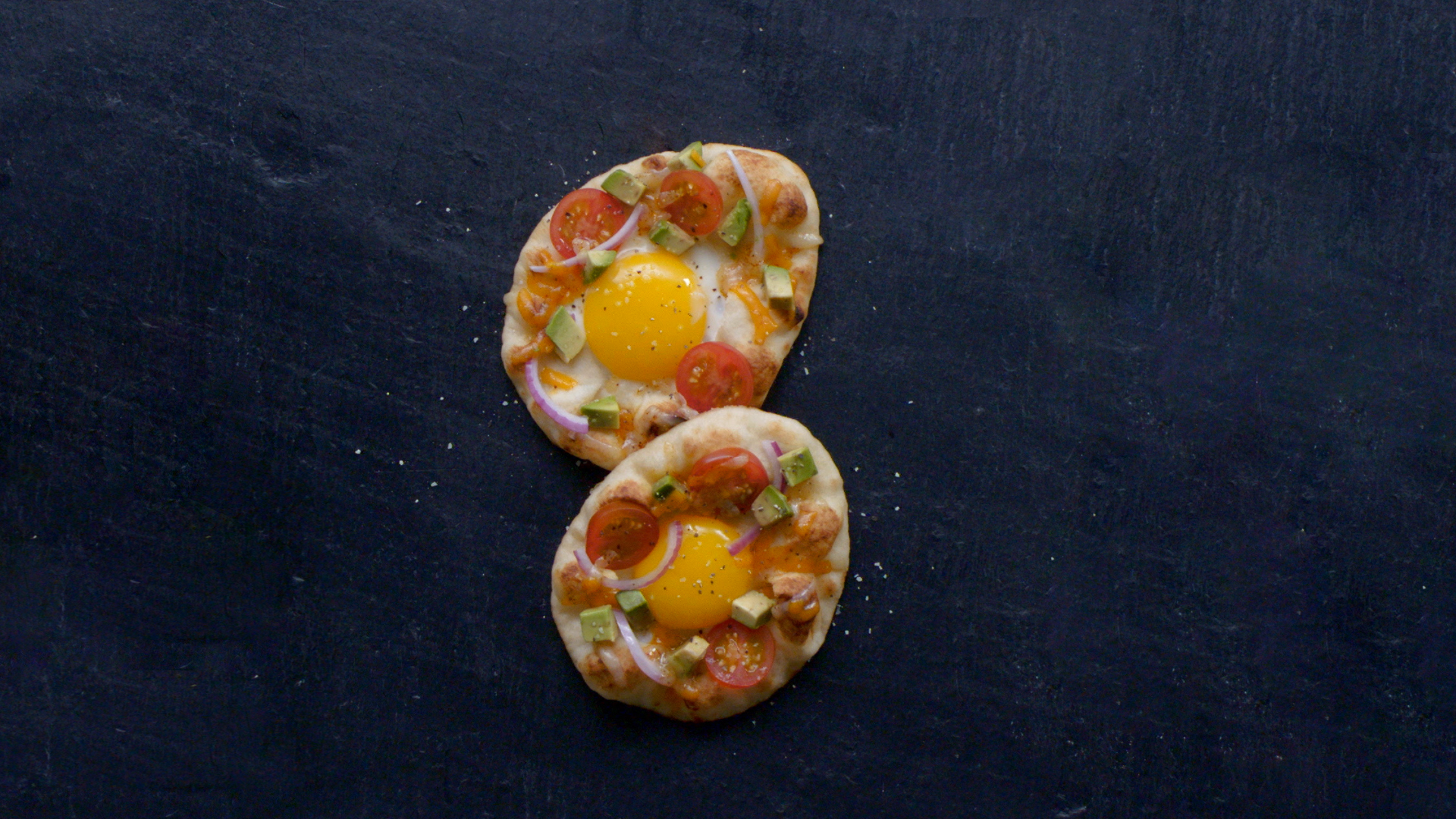 two Mini Naan 'Egg In The Hole' topped with tomatoes, avocado, onion and cheese.