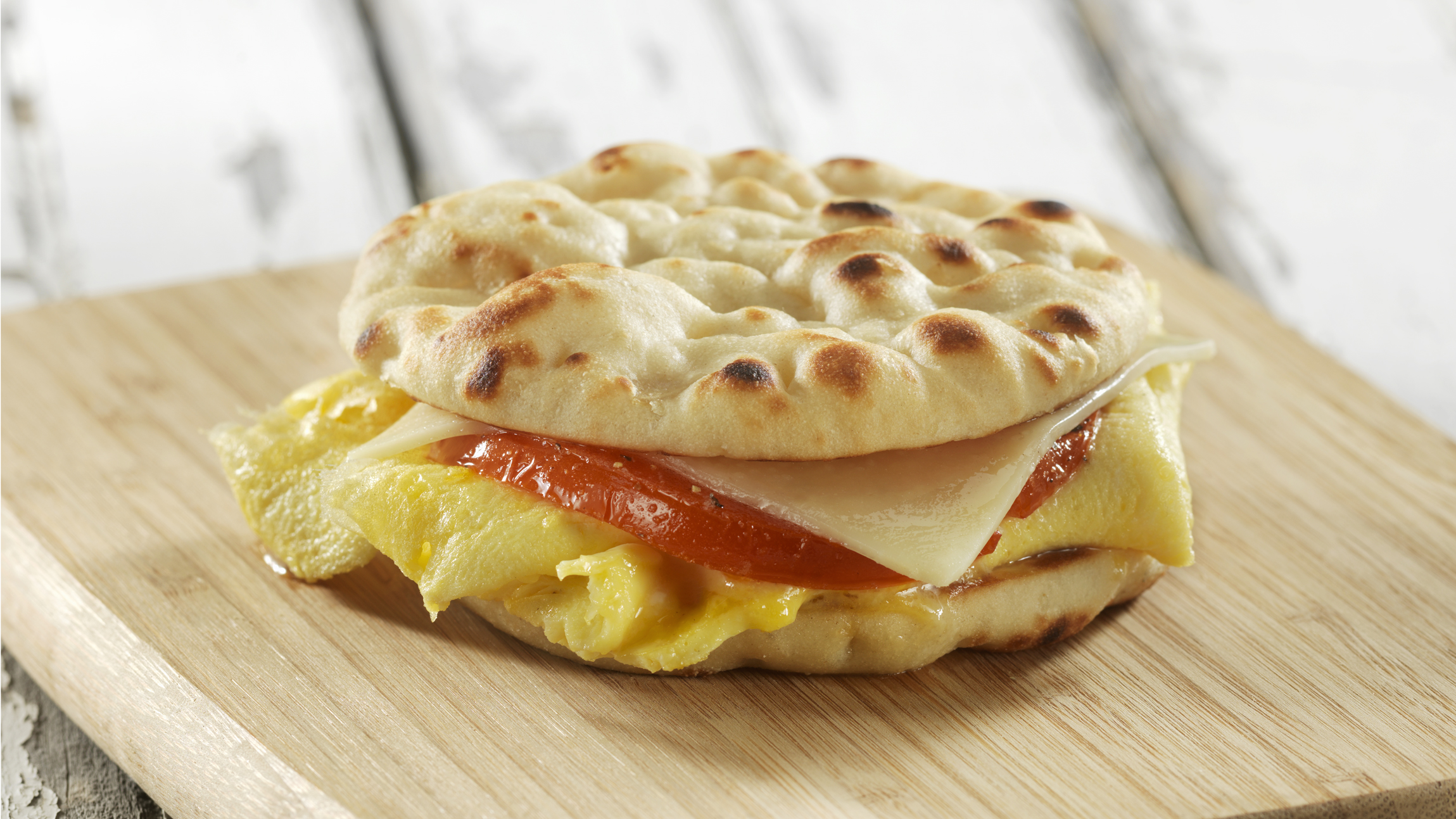 An easy and quick egg, cheese and tomato breakfast sandwich made with Stonefire Original Naan Rounds
